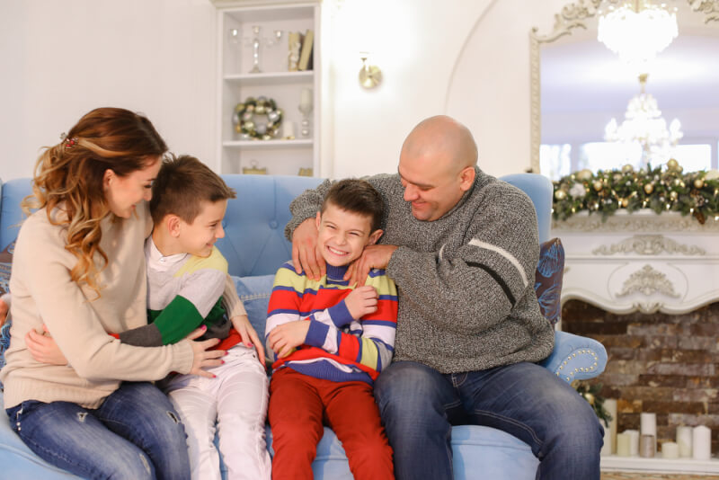 Family Fun New Year's Eve Party Ideas. Large and friendly family laughs and rejoices at New Year's holidays, loving parents affectionately tickle and family-like hugs boys of children, twin brothers, sitting on blue sofa with beautiful pillows christmas decorated with tall Christmas tree and fireplace in bright spacious room. Male European-looking children with short brown hair are dressed in brightly colored jumper, red and white jeans, European-looking woman with long blond curly hair dressed in beige sweater and dark blue jeans, man dressed in gray warm sweater and dark blue jeans. Concept of joint pastime of close-knit family, caring and love of parents for children, gifts and happy moments on holidays, eve of new year or Christmas.