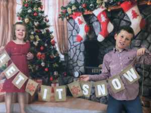 My kids with our Let-it-snow banner help save money for christmas