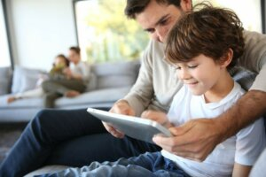 photo of parent with child playing with tablet and learning How to Develop Good Digital Habits in Your Kids