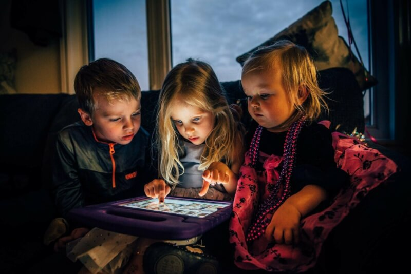 photo of kids looking at images on a tablet - Kids on Board: Must Know If Driving With Kids