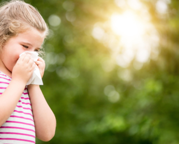 Photo of a young girl sneezing into tissue - Signs and Treatments of Hay Fever in Children