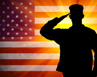 Proud saluting male army soldier on american flag background