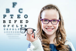 Close up portrait of young girl holding glasses with test chart in background -How to Help your Child Adjust to their New Glasses