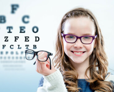 Close up portrait of young girl holding glasses with test chart in background - On Keeping Your Child's Eyes Healthy