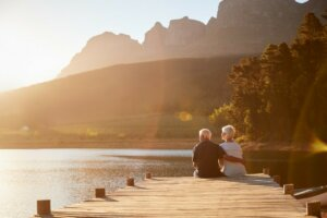 image of a retirement aged couple sitting on a dock enjoying the view 4 Ways to Create an Enjoyable Retirement