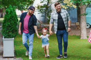 Travel Advice for LGBTQ Families - Little girl enjoying the walk with her fathers. Gay couple with daughter in the park.